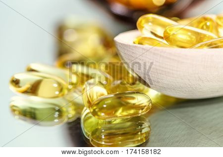 Wooden spoon of pills and oil fish capsules. Omega 3 pills fish oil capsules. Closeup fish oil dietary supplement. Horizontal