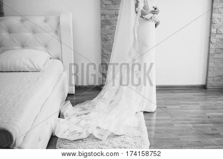 Black and white art photography monochrome buttoning wedding dress. Morning of the bride feminine style. Bridal Veil. Wedding gown