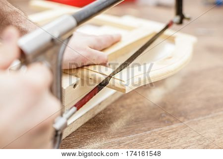 Man sawing a board with a hand saw wood close-up