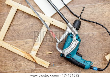 Power drill hacksaw and wood products lay on a floor ready to work