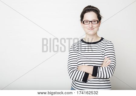 beautiful girl in glasses and a striped sweater and dark hair tucked away behind folded her arms and smiles