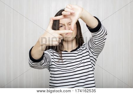 beautiful girl photographer looks through a frame made of finger close one eye wearing a striped sweater