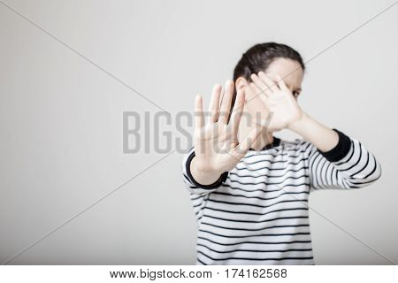 Girl put her hand forward and hiding her face stopping this gesture annoying photographer