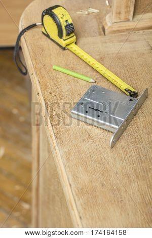 Mortise lock carpentry measuring tape and pencil are on old a sideboard