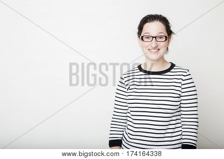 Attractive young woman in glasses and a striped sweater smiles and sneers