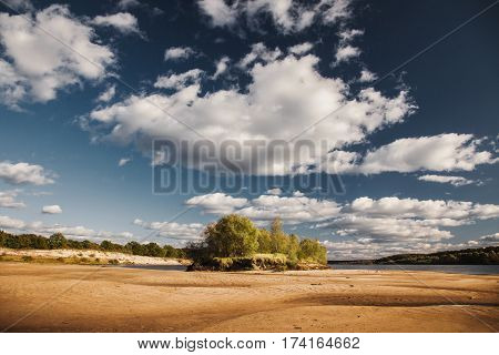 Rest on the nature. Beautiful summer nature landscape. The bright clear blue sky with white clouds in nature. Yellow sand on the beach in nature. Water surface. The river on the plain. Green nature foliage. Wild nature.