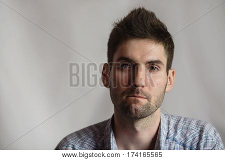 Young attractive cheerful man with dark hair with a beard in a shirt on a white background. Men's style. Male portrait