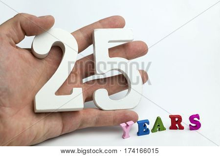 Hand holds a number twenty-five on a white background.
