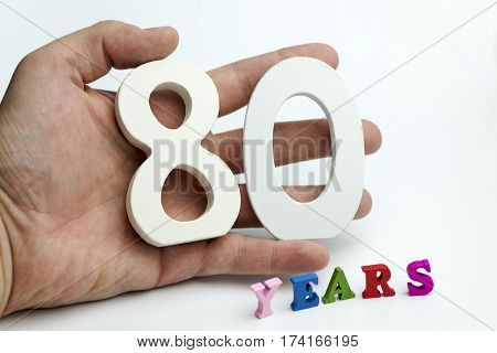 Hand holds a number eighty on white background.
