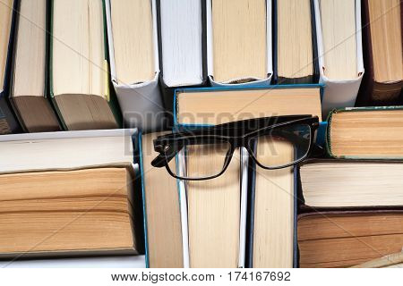 Old and used hardback books or text books seen from above. Books and reading are essential for self improvement gaining knowledge and success in our careers business and personal lives