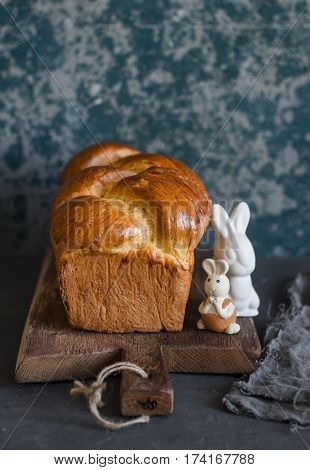Homemade brioche and ceramic easter rabbits on a rustic cutting board. Front view. Delicious pastries