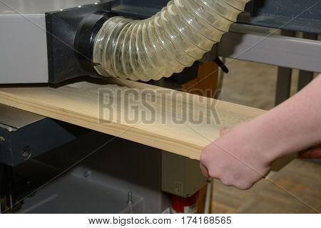Carpenter planing a wooden board on a planer machine - close-up