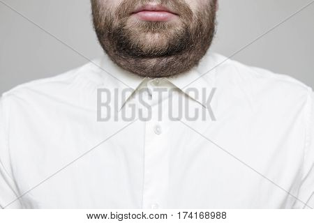 man in a white shirt with a double chin and beard on a gray background