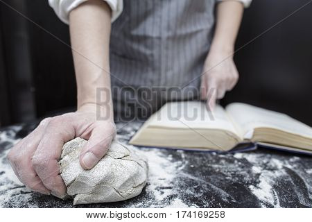 Baker chef looking for a recipe in a cookbook helping finger in the foreground is piece of dough on the black wooden table covered with flour