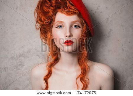 A woman with red hair and hat in a red dress. Red-haired girl with pale skin and blue eyes with a bright unusual appearance with a beret on her head on a gray background. French courtesan with red hat