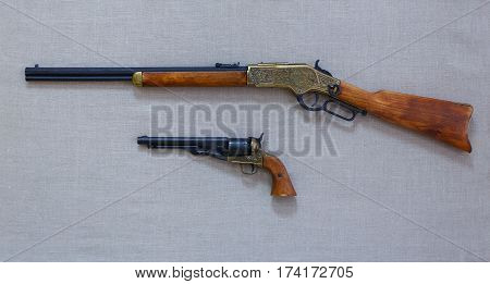 The old rifle and a gun with wooden and metal pieces are on the fabric background.