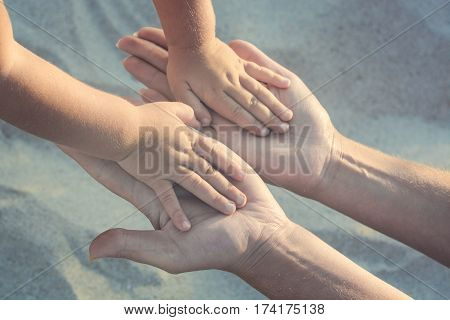 Mother and small baby play with sand. Baby hold her hands to the mothers arms. Active parents and people outdoor activity on summer vacations with children.