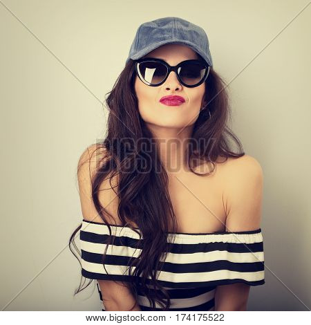 Happy Grimacing Young Woman In Sunglasses And Blue Baseball Cap Posing In Striped Blouse. Closeup Vi