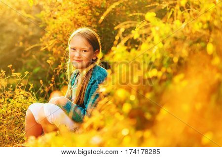 Outdoor portrait of a cute little 8-9 year old girl at sunset