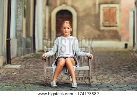 Stylish 8-9 year old kid girl sitting on a small bench in old town, wearing grey cardigan, white t-shirt and silver shoes