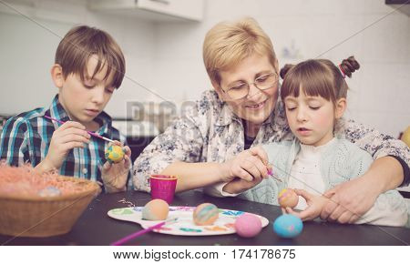 Grandmother with grandchildren are coloring eggs for Easter