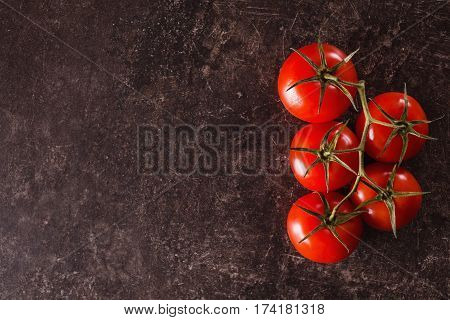 Food on table. Red tomatoes lie on a dark marble table. Space for text and design. Flat lay food copyspace. Healthy food. Food on a dark background. Summer tasty food.