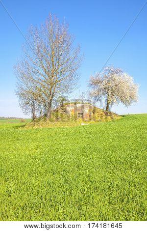 Old military bunker, blue sky, green field
