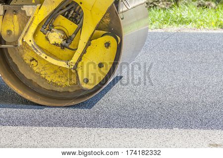 Road roller flattening new asphalt, industrial place