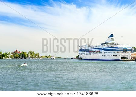 Cargo-passenger cruise ferry moored in Bay at pier in Helsinki port. Waiting for passengers boarding from terminal and loading of vehicles and cargo. Scandinavia Suomi Helsingfors