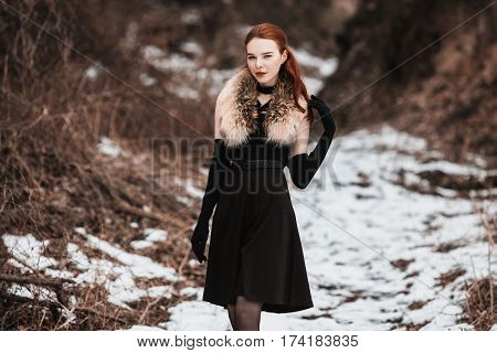 Striking lady girl with long red hair in black clothes. Woman lady in black dress and fur around neck with long black gloves posing on background of winter nature. Female lady street style. Beautiful elegant model