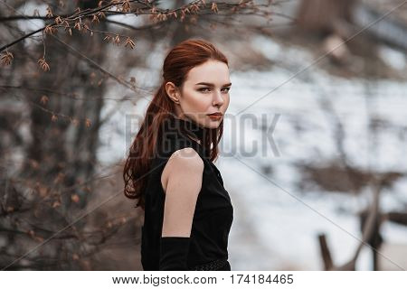Portrait of glamorous girl with long red hair in black clothes. Woman in black dress and long black gloves posing on a background of winter autumn nature. Female street style. Beautiful elegant model