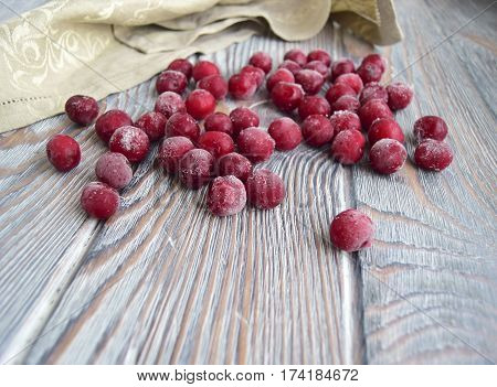 The frozen cherries lie on a wooden table. Natural products of the nature. Cherries are covered with hoarfrost