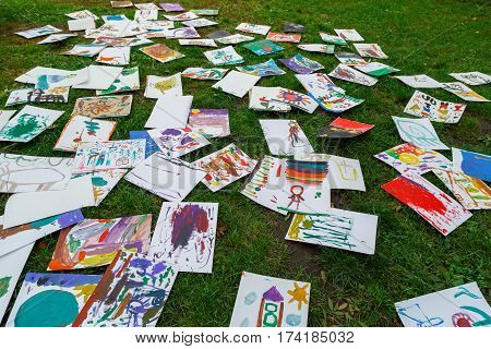 A lot of children's drawings scattered on the grass.