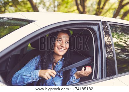Closeup Portrait Of Happy Woman Pulling On Seatbelt Inside White Car, Toned