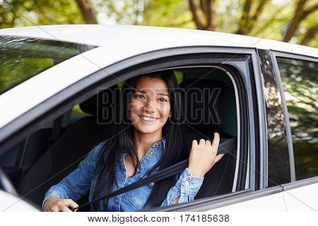 Young Woman Fasten Seat Belt In Her Car