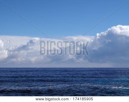 Shallow ocean waters of Windward side of Oahu looking into the pacific ocean and clouds.