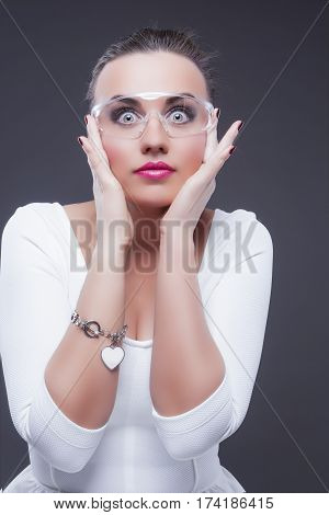 Portrait of Expressive Surprised Caucasian Brunette Woman With Both Hands Lifted Near Face. Against Gray Background.Vertical Image