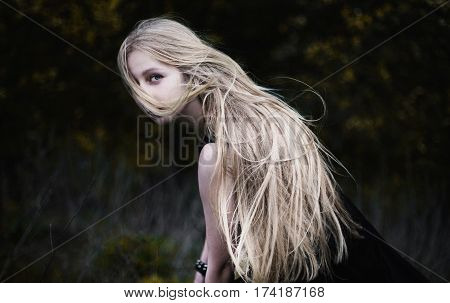Blonde girl with very long hair on dark fone. Woman portrait. Conceptual photography. The blonde girl's face is covered with hair. Blonde woman