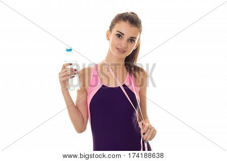 attractive young girl sports swimsuit looks straight and holding a water bottle isolated on white background
