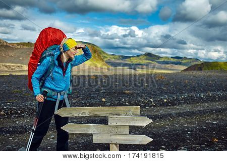 woman hiker on the trail in the Islandic mountains. woman standing and posing near pointer against the backdrop of a desert mountain landscape. Treking in National Park Landmannalaugar, Iceland. Travel photography concept