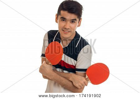 young brunette sportsman with tennis rackets practicing ping pong isolated