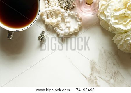 Chic and elegant styled bathroom vanity with coffee, vintage jewelry, flowers and perfume. Open white marble space for copy.