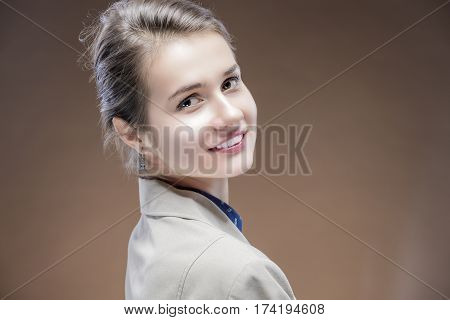 Portrait of Young Sensual Caucasian Girl in Jacket Looking backwards and Smiling. Against Brown Background. Horizontal Image Orientation