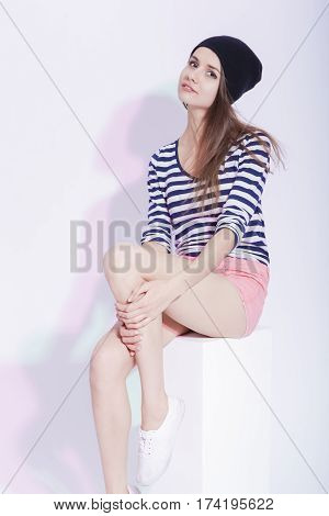 Youth fashion Concepts and Ideas. Seriuos and Calm Caucasian Slim Brunette in Hat Posing On White Box in Studion Against White.Vertical Image