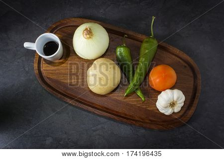 A photo from above of random vegetables on a wooden plate.