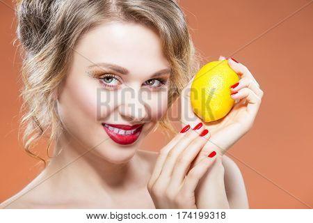 Sexy Fruit Series. Closeup Portrait of Happy Naked Caucasian Blond Girl With Lemon Fruit. Against Orange Background. Horizontal Image