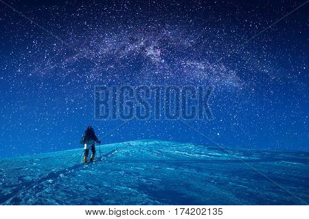 A climber climbs up a snowy at night. Milky way in a starry sky above the mountain top.