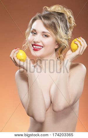 Fruit Series. Sensual Caucasian Blond Girl Posing with Two Lemons in Hands. Lifted Hands. Against Orange Background. Vertical Image Composition