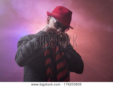 Portrait image of a mature jazz man with a harmonica