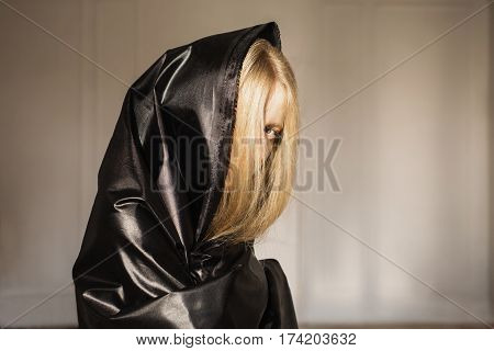 Art conceptual image. The conceptual girl with long blonde hair. Woman in black cloth with a piercing look. Conceptual photography. Anonymity. Conceptual portrait. Conceptual idea